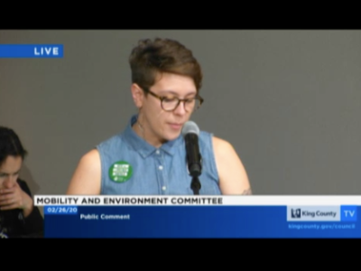 A screenshot of the King County Council's Mobility And Environment Committee live stream where Kelsey (a brunette with boy-short hair, buzzcut on one side, wearing black glasses) is talking into a mic. She is wearing a denim button-up, collared tank which has a green-and-white button pinned near her right shoulder.