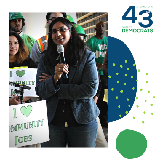 """Seattle City Councilmember Kshama Sawant stands, holding a mic and smiling with people behind her holding """"I love community jobs"""" signs."""