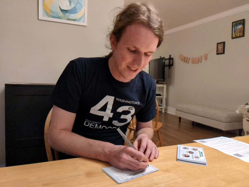 43rd District Democrats Chair Scott Alspach happily writes on one of the postcards.